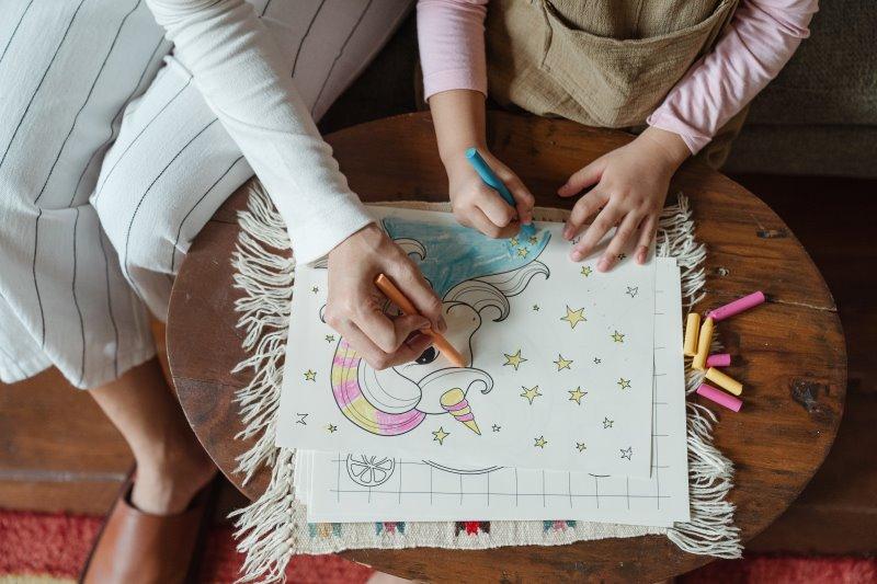 Mutter und Kind zeichnen mit Buntstiften ein Bild