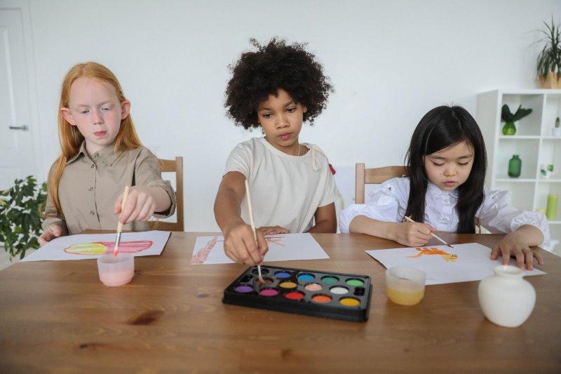 Drei Kinder malen Bilder mit Aquarellpinsel und Wasserfarben