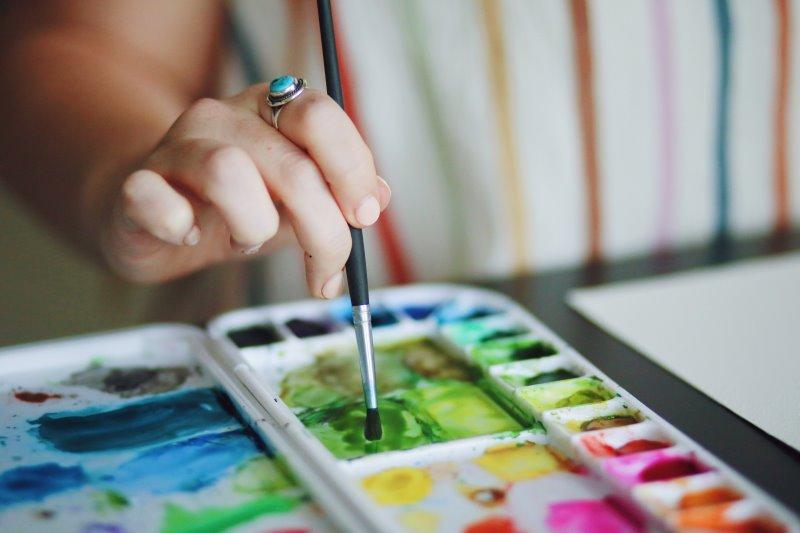 Eine Person mischt Wasserfarbe mit einem Aquarellpinsel in einer Mischpalette.