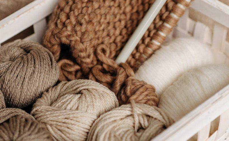 verschiedene Wollknäule und der Anfang eines Pullovers in einem Körbchen
