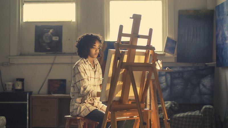 Frau malt im sitzen an einem Gemälde