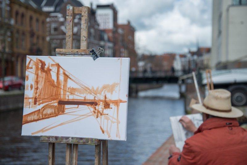 Mann malt an einem Gemälde im Freien