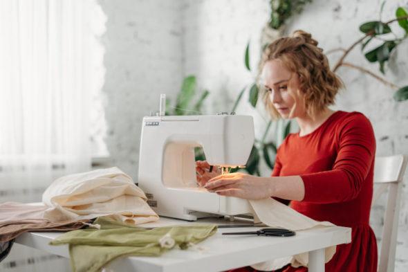 Frau beim Nähen mit einer Freiarm-Nähmaschine