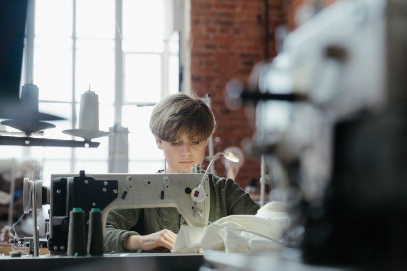 Kind näht konzentriert an Nähmaschine